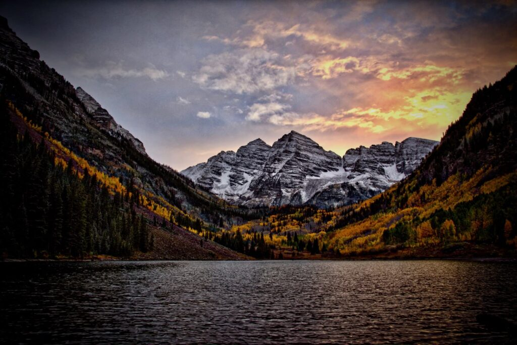 Mounatain lake lined with yellow Aspen trees in fall with snowcapped mountain in background